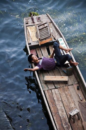 Oriantal man sleeping accross fishing boat